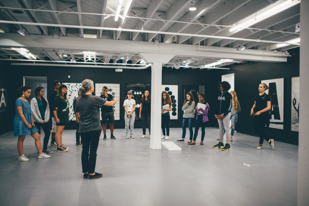 Image of the artist and photographer Shannon Ebner touring students from Young Artists Initiative, ICA Miami