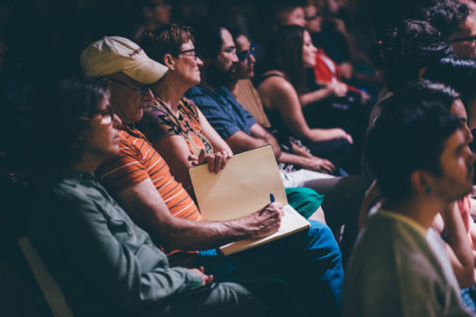 Image of an audience member taking notes during a lecture by Richard Tuttle for ICA Speaks, ICA Miami